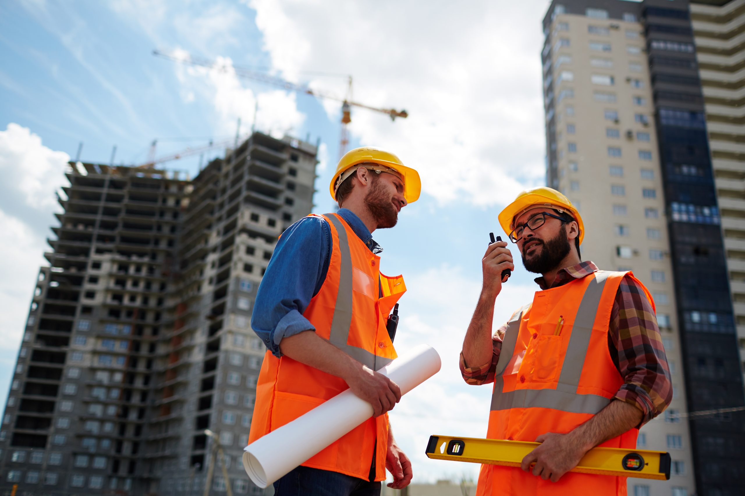 Contractor speaking on walkie-talkie with co-worker near by